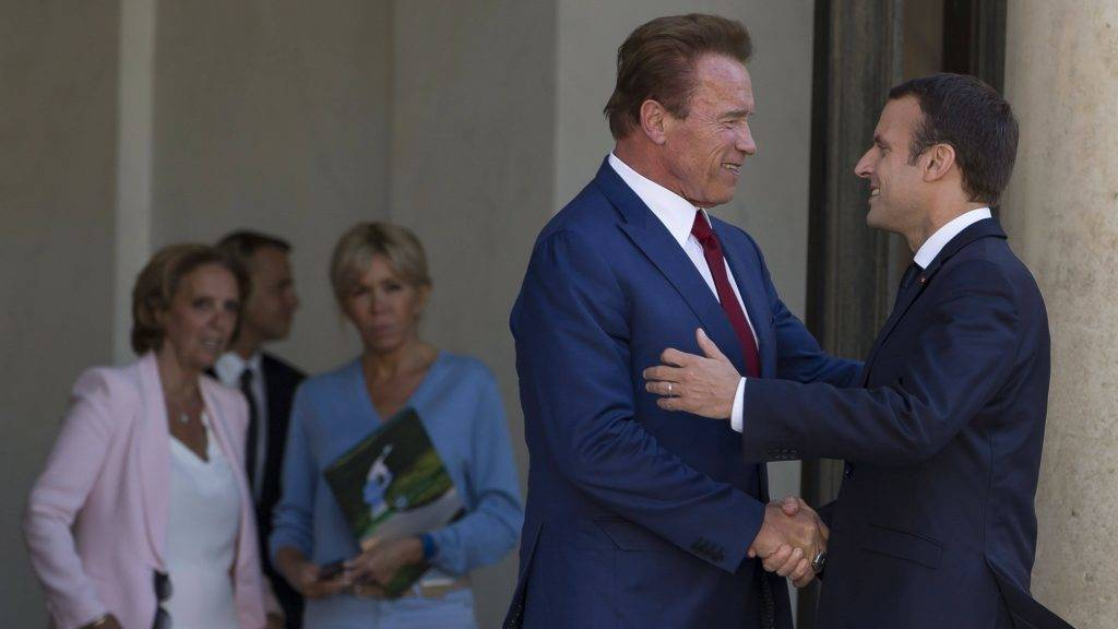 Párizs, 2017. június 23. Emmanuel Macron francia elnök (j) fogadja Arnold Schwarzenegger amerikai színészt, volt kaliforniai kormányzót a párizsi államfõi rezidencia, az Elysée-palota bejáratánál 2017. június 23-án. A háttérben jobbra Macron felesége, Brigitte Trogneux. (MTI/EPA/Ian Langsdon)