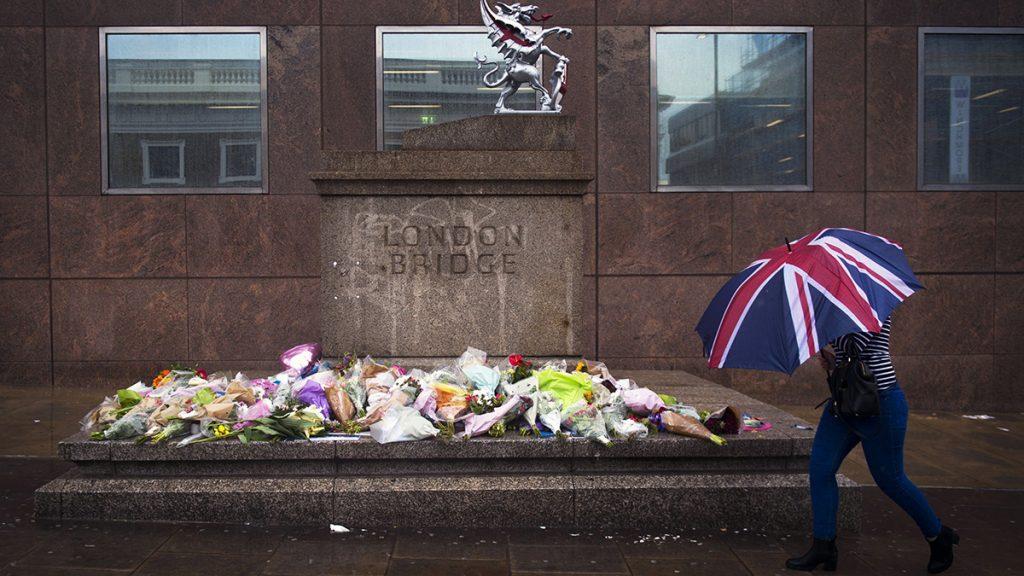 London, 2017. június 6.A londoni merénylet áldozatainak a London Bridge belvárosi hídnál rögtönzött emlékhelye előtt egy el egy járókelő 2017. június 6-án. Három férfi június 3-án éjjel gyalogosok közé hajtott furgonnal a hídon, majd a közeli piac, a Borough Market környékén késsel támadt a járókelőkre. Hét ember életét vesztette, negyvennyolc megsebesült. (MTI/EPA/Will Oliver)