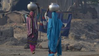 Pakistani women carry pots with water on their heads on the outskirts of Lahore on March 21, 2017, ahead of World Water Day. International World Water Day is marked annually on March 22 to focus global attention on the importance of water. / AFP PHOTO / ARIF ALI