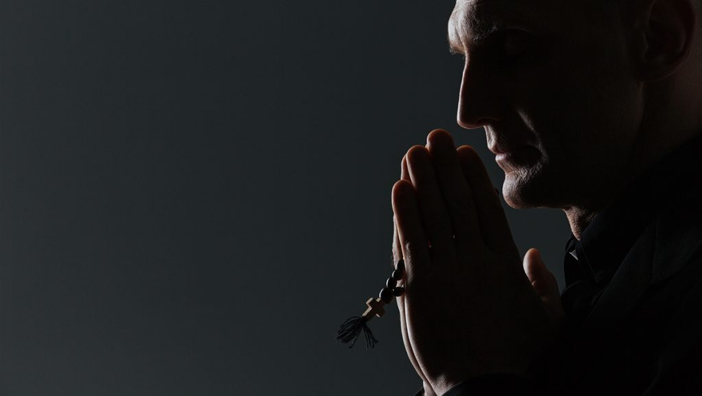 Silhouette of man holding rosary and praying over black background