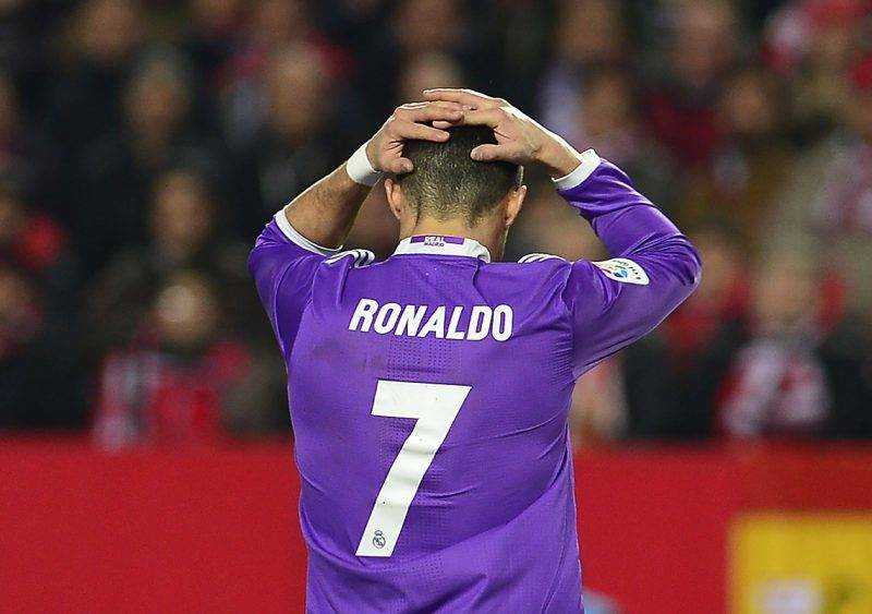 (FILES) This file photo taken on January 15, 2017 shows Real Madrid's Portuguese forward Cristiano Ronaldo holding his head after missing a goal opportunity during the Spanish league football match Sevilla FC vs Real Madrid CF at the Ramon Sanchez Pizjuan stadium in Sevilla on January 15, 2017. State prosecutors have filed a complaint on June 13, 2017 against the Portuguese star, who they accuse of taking advantage of a corporate structure to defraud the Spanish Treasury of 14.7 million euros / AFP PHOTO / CRISTINA QUICLER