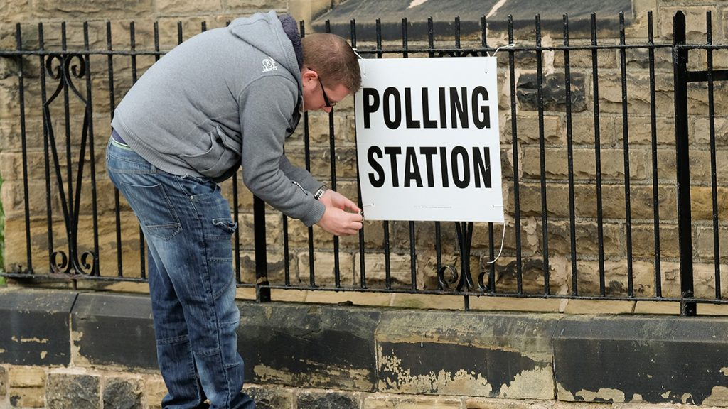 SALTBURN-BY-THE-SEA, UNITED KINGDOM - JUNE 08: A polling station offical attaches a sign to railings as the polls open on June 8, 2017 in Saltburn-by-the-Sea, United Kingdom. Polling stations open across the country as the United Kingdom goes to the polls to vote in the 2017 general election. (Photo by Ian Forsyth/Getty Images)