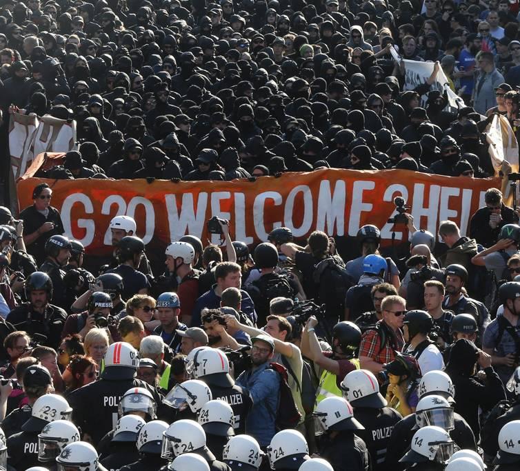 """Hamburg, 2017. július 6.A világ 19 legfejlettebb gazdaságú és vezető feltörekvő országát, valamint az Európai Uniót tömörítő húszas csoport, a G20 hamburgi csúcstalálkozója ellen tiltakozó tüntetők és rohamrendőrök az """"Üdvözlünk a pokolban!"""" elnevezésű tiltakozáson az észak-németországi város halpiacán 2017. július 6-án, egy nappal a csúcstalálkozó kezdete előtt. (MTI/AP/Michael Probst)"""
