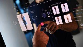 Oak Labs engineer Wesley Bliss demonstrates their interactive touchable mirror inside a makeshift dressing room at their office in New York on February 7, 2017.   Oak Fitting Room, equipped with an interactive touchable mirror, delivers advanced technology to the retail world. Shoppers can tap on the mirror to request a different size or color of corresponding items or to seek assistance from an associate.   / AFP PHOTO / Jewel SAMAD