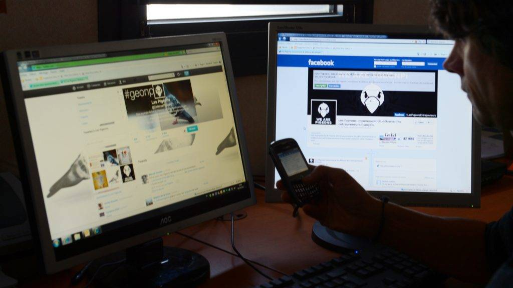 """A person looks at tweets sent on the """"defensePigeons"""" Twitter account of the self-employed entrepreneurs (auto-entrepreneurs) protest front page on the Facebook website, on October 4, 2012 in Tours, western France. Entrepreneurs and self-employed entrepreneurs organisations denounced the day before the lack of information and dialogue regarding an increase in employees' social security contributions presented in the French 2013 budget project.  AFP PHOTO / ALAIN JOCARD / AFP PHOTO / ALAIN JOCARD"""