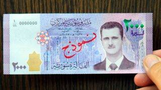 """A handout picture released by the official Syrian Arab News Agency (SANA) on July 2, 2017 shows Syria's newly announced 2,000 pound note, featuring a portrait of President Bashar al-Assad, displayed during a press conference in the capital Damascus.  The Syrian Central Bank has released the war-ravaged country's largest currency note yet, featuring the face of President Bashar al-Assad for the first time. The new 2,000 pound note went into circulation in several regions including the capital Damascus on Sunday, according to Central Bank governor Duraid Dergham. / AFP PHOTO / SANA / - /  == RESTRICTED TO EDITORIAL USE - MANDATORY CREDIT """"AFP PHOTO / HO / SANA"""" - NO MARKETING NO ADVERTISING CAMPAIGNS - DISTRIBUTED AS A SERVICE TO CLIENTS =="""