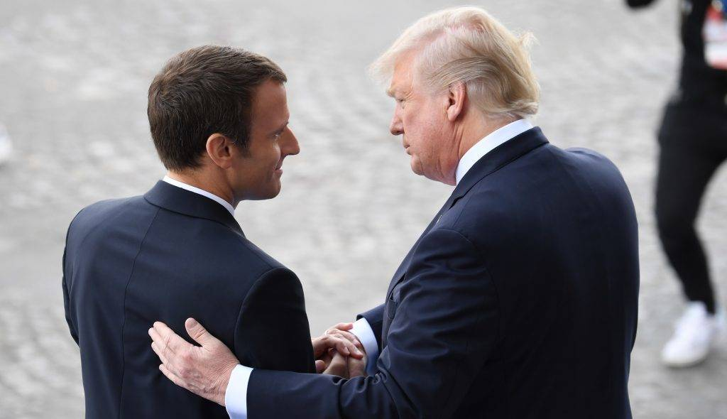 French President Emmanuel Macron (L) bids farewell to his US counterpart Donald Trump after the annual Bastille Day military parade on the Champs-Elysees avenue in Paris on July 14, 2017. Bastille Day, the French National Day, is held annually each July 14, to commemorate the storming of the Bastille fortress in 1789. This years parade on Paris's Champs-Elysees will commemorate the centenary of the US entering WWI and will feature horses, helicopters, planes and troops. / AFP PHOTO / ALAIN JOCARD