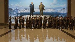 In a photo taken on July 19, 2017 Korean People's Army (KPA) soldiers walk past portraits of late North Korean leaders Kim Il-Sung (L) and Kim Jong-Il (R) at the Korean Revolutionary Museum in Pyongyang.  / AFP PHOTO / Ed JONES