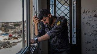 A commander ofthe Syrian Democratic Forces (SDF) communicates with soldiers on a radio in Al Sinaa, eastern Raqqa, Syria, 05 July 2017. Raqqa is the capital of IS in Syria Photo: Morukc Umnaber/dpa