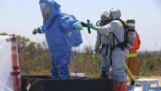 Marine Corps Base Camp Pendleton, California - An airman stands in a tub of cleaning solution while being rinsed off during a decontamination process at the annaul All Hazards Protection Exercise. The exercise included several events such as the testing of emergency notification systems, execution of area barrier plans, activation of the base crisis action team, a simulated incident in the 32 Area and the establishment of an evacuation shelter.