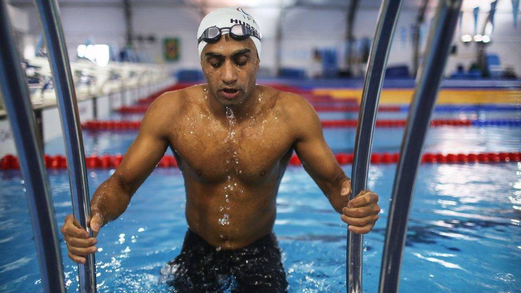RIO DE JANEIRO, BRAZIL - SEPTEMBER 17:  Syrian refugee swimmer Ibrahim Al Hussein prepares to exit the pool during a practice session for media in a training pool during the Rio 2016 Paralympic Games at Olympic Park on September 17, 2016 in Rio de Janeiro, Brazil. The swimmer lost part of his leg during a rocket attack in war-torn Syria as he was trying to save a friend injured in a bombing nearby. He fled the war to Turkey and eventually boarded a rubber dinghy to cross the Aegean Sea to Greece, where he currently resides. Al Hussein competed in the men's 50 meter and 100 meter freestyle swimming contests during the Games.  (Photo by Mario Tama/Getty Images)