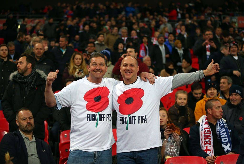 LONDON, ENGLAND - NOVEMBER 11: (EDITORS NOTE: Image contains profanity.) Fans wearing a poppy shirt protesting against FIFA during the FIFA 2018 World Cup Qualifier between England and Scotland at Wembley Stadium on November 11, 2016 in London, England. (Photo by Catherine Ivill - AMA/Getty Images)