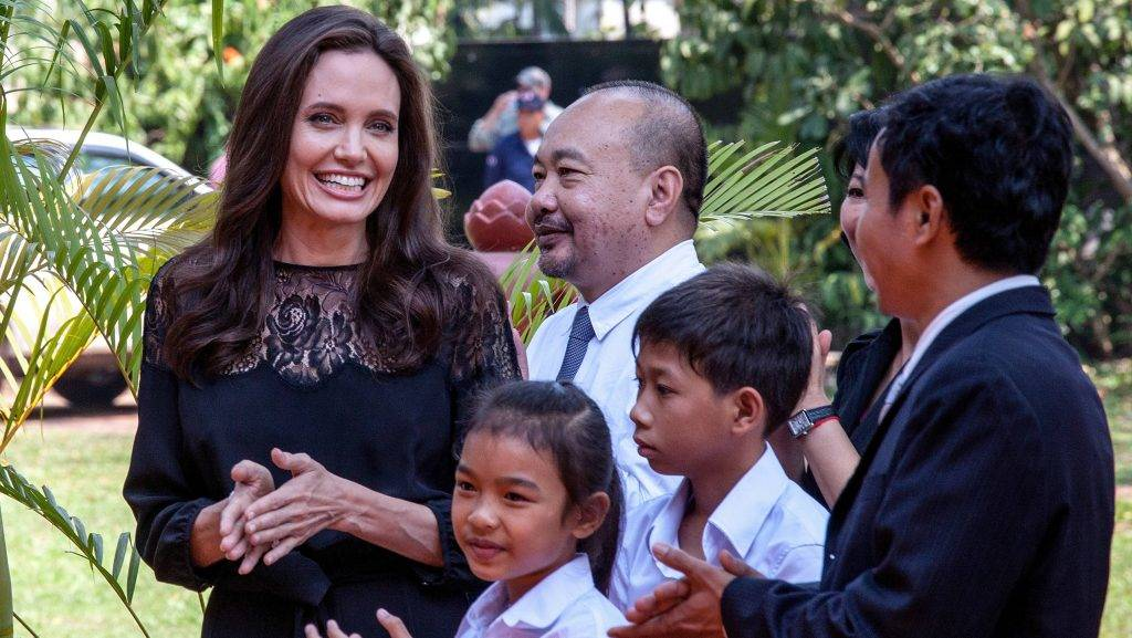 """SIEM REAP, CAMBODIA - FEBRUARY 18:  Angelina Jolie (left) and producer Rithy Panh (center) chat with actors before holding a press conference ahead of the premiere of their new film """"First They Killed My Father"""" set up at the Raffles Grand Hotel D'Angkor on February 18, 2017 in Siem Reap, Cambodia. Angelina Jolie is in Siem Reap for the world premiere of her new movie, """"First They Killed my Father,"""" a Netflix-produced adaption of the autobiography by the same name penned by Loung Ung, who lived through the Khmer Rouge regime as a young child. The film will be screened Saturday night in the Angkor Wat temple complex, and released later this year on Netflix. (Photo by Omar Havana/Getty Images)"""