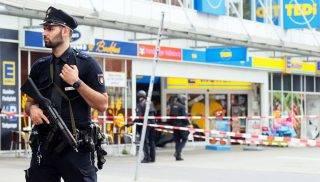Hamburg, 2017. július 28. Rendõr áll egy hamburgi szupermarket bejárata elõtt 2017. július 28-án, miután a bevásárlóközpontban egy férfi késsel rátámadt a vásárlókra, több embert megsebesített, majd elmenekült. Egy ember meghalt, a feltételezett elkövetõt õrizetbe vették. (MTI/EPA/Marius Röer)