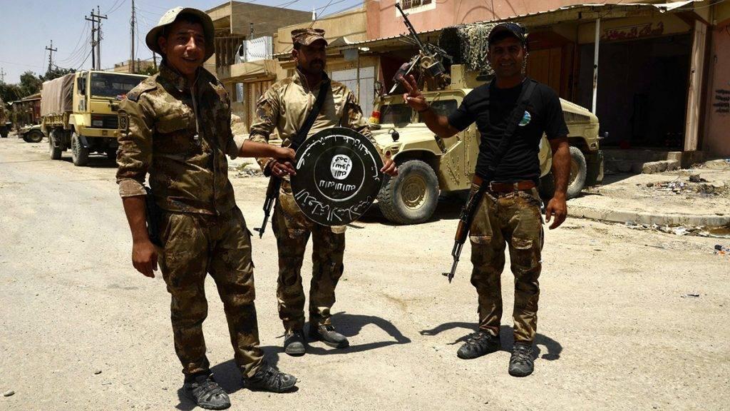 Moszul, 2017. június 18.Iraki katonák az Iszlám Állam dzsihadista terrorszervezet zászlajával Moszul egyik nyugati negyedében, Sifában 2017. június 17-én. Az iraki hadsereg közlése szerint 2017. június 18-án az iraki erők megkezdték az előrenyomulást Moszul dzsihadisták kezén lévő óvárosában.  (MTI/EPA/Omar Alhajali)