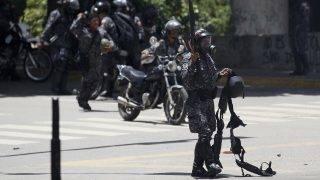 Caracas, 2017. július 30. Sebesült társa fegyverövét fogja egy nemzeti gárdista tüntetõkkel vívott összecsapások során Caracasban 2017. július 30-án, a venezuelai alkotmányozó nemzetgyûlési választások napján. A fõvároson kívül Lara, Mérida és Táchira szövetségi államokban is erõszakos összetûzések kísérik a voksolást. (MTI/AP/Ariana Cubillos)