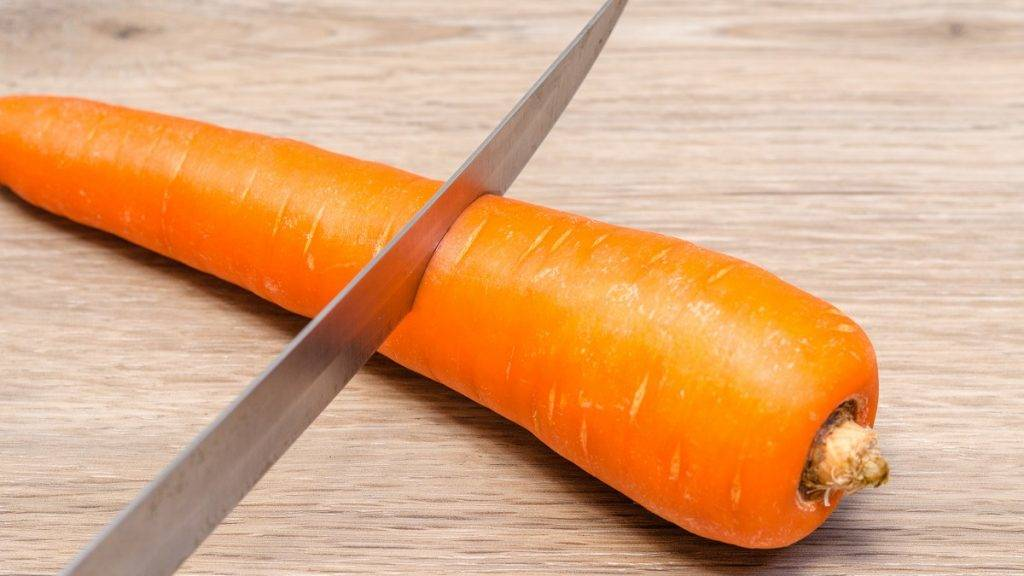 chopping carrot on wooden board