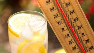 Warm summer day, thermometer next cold lemonade  showing high temperature