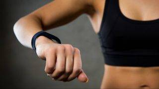 sport, fitness, technology and people concept - close up of young woman with heart-rate watch in gym