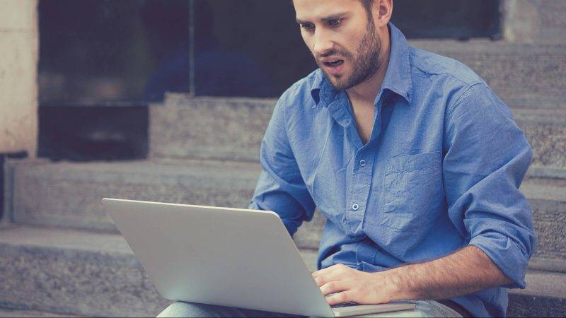 Handsome worried man working on laptop computer sitting on stairs outside corporate building