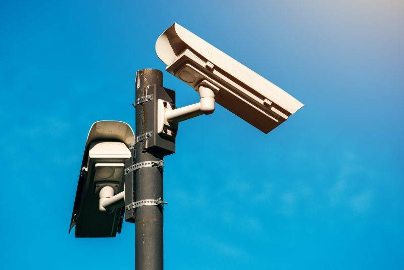 CCTV camera, modern era anti-terrorist electronic surveillance security cameras against blue sky that symbolizes freedom