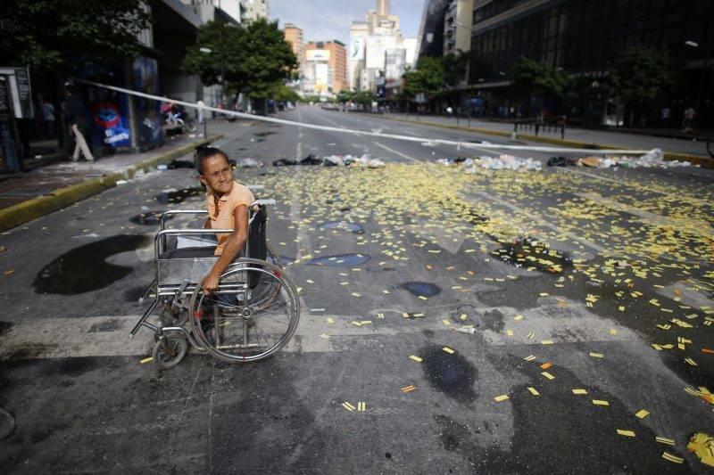 Caracas, 2017. július 20. Kerekesszékes nõ egy metrójegyek borította úttesten a Nicolás Maduro venezuelai elnök alkotmánymódosítási törekvéseit ellenzõ 24 órás, általános sztrájk idején Caracasban 2017. július 20-án. 2002 óta elõször tartanak általános munkabeszüntetést a súlyos infláció és élelmiszerhiány sújtotta dél-amerikai országban. (MTI/AP/Ariana Cubillos)
