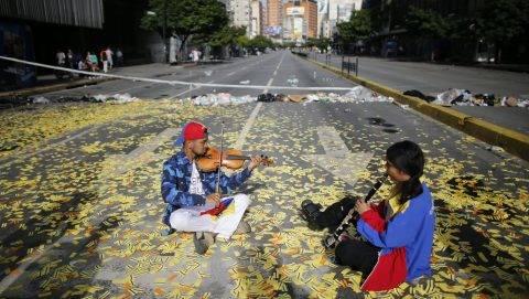Caracas, 2017. július 20. Zenészek játszanak egy metrójegyek borította úttesten a Nicolás Maduro venezuelai elnök alkotmánymódosítási törekvéseit ellenzõ 24 órás, általános sztrájk idején Caracasban 2017. július 20-án. 2002 óta elõször tartanak általános munkabeszüntetést a súlyos infláció és élelmiszerhiány sújtotta dél-amerikai országban. (MTI/AP/Ariana Cubillos)