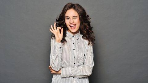 Portrait of attractive brunette businesswoman indicating OK sign isolated on white background. she is happy because it has successfully completed the task