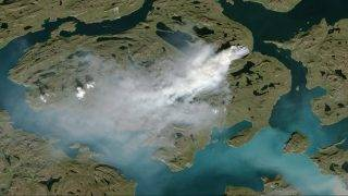 """This NOAA handout satellite photo taken on August 3rd, 2017 shows a cloud of smoke from wildfires burning in western Greenland, about 150 kilometers (90 miles) northeast of Sisimiut.   It is not clear what triggered this fire, though a lack of documented lightning prior to its ignition suggests the fire was probably triggered by human activity. The area is regularly used by reindeer hunters, and is not too far from a town with a population of 5,500 people. The summer has been quite dry. Sisimiut saw almost no rain in June and half of the usual amount in July. That may have parched dwarf willows, shrubs, grasses, mosses, and other vegetation that commonly live in Greenland's coastal areas and made them more likely to burn.  / AFP PHOTO / NOAA / Handout / RESTRICTED TO EDITORIAL USE - MANDATORY CREDIT """"AFP PHOTO / NOAA/HANDOUT"""" - NO MARKETING NO ADVERTISING CAMPAIGNS - DISTRIBUTED AS A SERVICE TO CLIENTS"""