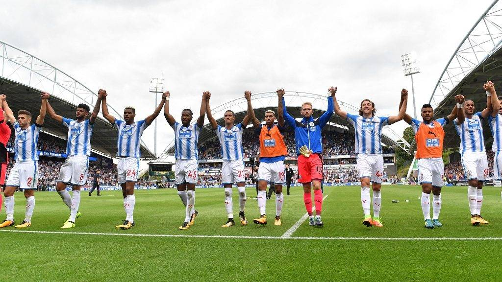 Huddersfield Town players celebrate victory after the English Premier League football match between Huddersfield Town and Newcastle United at the John Smith's stadium in Huddersfield, northern England on August 20, 2017. Huddersfield Town beat Newcastle United 1-0. / AFP PHOTO / Anthony Devlin / RESTRICTED TO EDITORIAL USE. No use with unauthorized audio, video, data, fixture lists, club/league logos or 'live' services. Online in-match use limited to 75 images, no video emulation. No use in betting, games or single club/league/player publications.  /