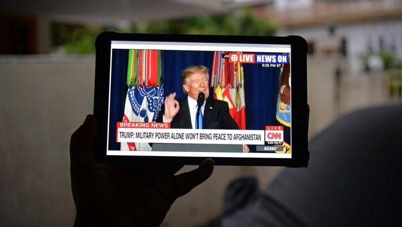 """A Pakistani resident watches his tablet device in Islamabad on August 22, 2017, showing a live broadcast of US President Donald Trump delivering his address from Joint Base Myer-Henderson Hall in Arlington, Virginia in the US.  President Donald Trump warned Pakistan that Washington will no longer tolerate Pakistan offering """"safe havens"""" to extremists. Trump suggested that military and other aid to Washington's nuclear-armed ally is at stake if it does not clamp down on extremism.  / AFP PHOTO / AAMIR QURESHI"""