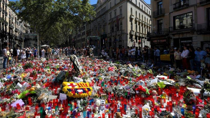 People display flowers and candles to pay tribute to the victims of the Barcelona and Cambrils attacks on the Rambla boulevard in Barcelona on August 22, 2017, five days after the attacks that killed 15 people.  An alleged member of the terror cell that unleashed carnage in Spain last week admitted to a judge Tuesday that he and other suspects had planned a bigger attack, a judicial source said. / AFP PHOTO / LLUIS GENE