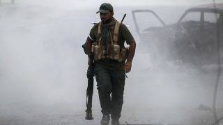 A fighter of the Hashed Al-Shaabi (Popular Mobilization units) walks through the dust carrying a rocket-propelled grenade (RPG) launcher, during the advance through the town of Tal Afar, west of Mosul, after the Iraqi government announced the launch of the operation to retake it from Islamic State (IS) group control, on August 26, 2017. / AFP PHOTO / AHMAD AL-RUBAYE