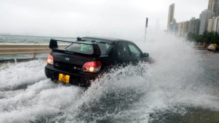 (170823) -- HONG KONG, Aug. 23, 2017 (Xinhua) -- A car wades through a waterlogged road in Hong Kong, south China, Aug. 23, 2017. Hato, the 13th typhoon to hit China this year, made landfall in the city of Zhuhai in southern China's Guangdong Province at noon Wednesday. Influenced by outer rainband of Hato, strong wind and rain affected Hong Kong and a tropical cyclone warning was issued by Hong Kong Observatory. (Xinhua/Li Peng) (wyl)