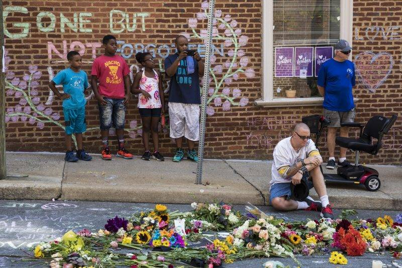 CHARLOTTESVILLE, USA - AUGUST 16: People stop to pay their respects at a memorial for Heather Heyer and the other victims at the intersection where James Alex Fields Jr., a White Supremacist, drove his car into a crowd of counter-protestors, killing Heyer and wounding 19 others last Saturday, in Charlottesville, Virginia, United States on August 16, 2017. Samuel Corum / Anadolu Agency