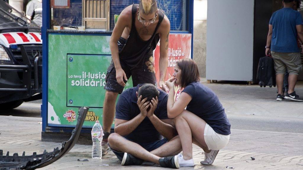Barcelona, 2017. augusztus 17. Sebesült férfi mellett emberek Barcelonában 2017. augusztus 17-én, miután egy fehér furgon járókelõk közé hajtott a járdára a katalán fõváros Las Ramblas negyedében. Legalább egy ember életét vesztette, harmincketten megsebesültek. (MTI/EPA/David Armengou)