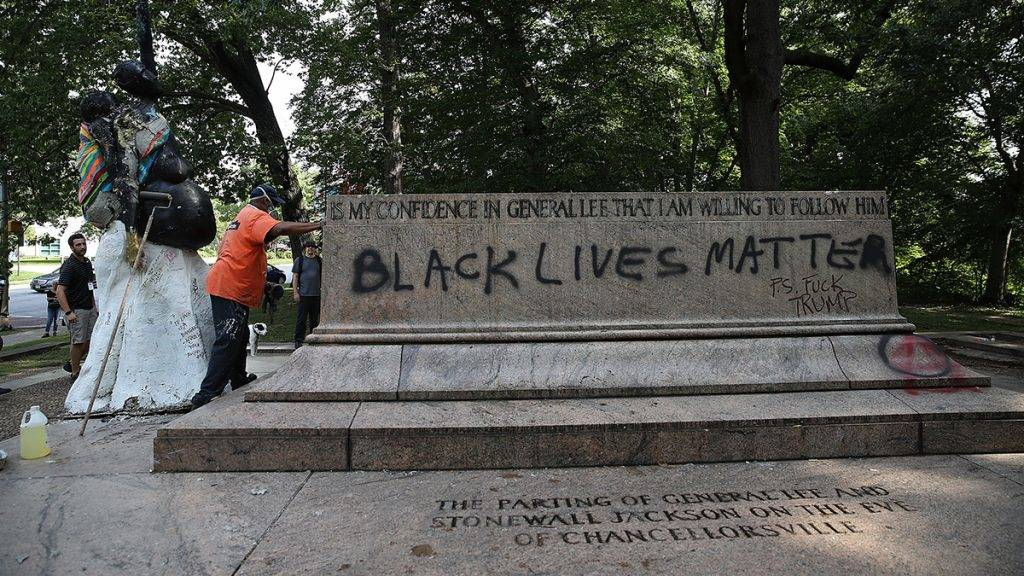 """BALTIMORE, MD - AUGUST 16:  Baltimore city workers remove graffiti from the pedestal where a statue dedicated to Robert E. Lee and Thomas """"Stonewall"""" Jackson stood August 16, 2017 in Baltimore, Maryland. The City of Baltimore removed four statues celebrating confederate heroes from city parks overnight, following the weekend's violence in Charlottesville, Virginia.  (Photo by Win McNamee/Getty Images)"""