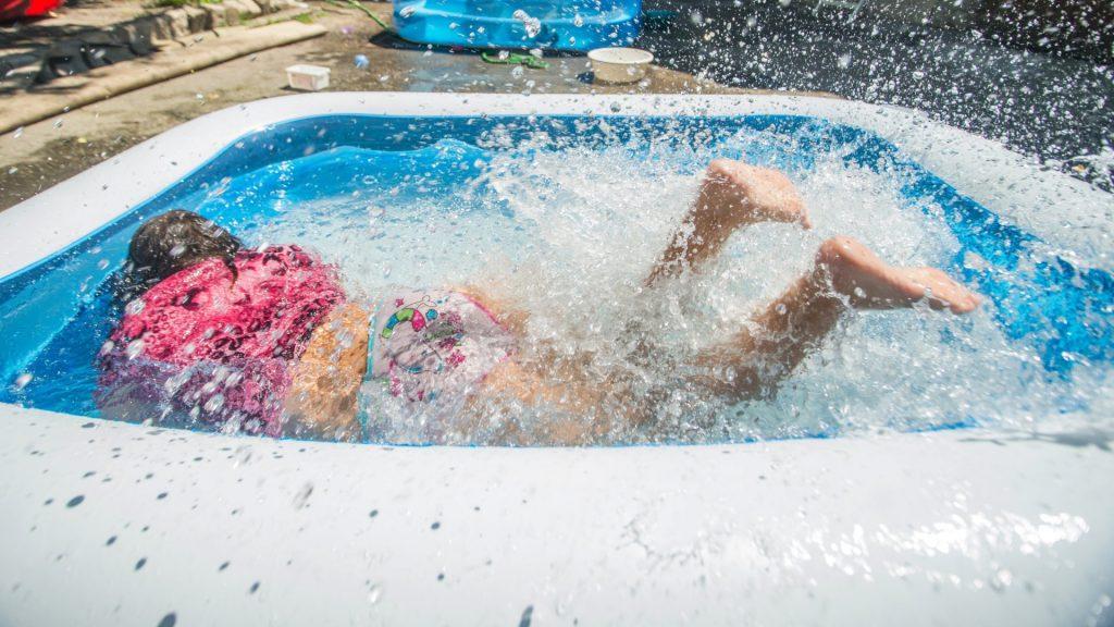 Hőség - Gyerek hűsölnek egy belvárosi bérház udvarán