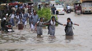 Újdelhi, 2017. augusztus 9. Iskolai egyenruhás lányok térdig érõ vízben gázolnak a monszunesõk által elárasztott utak egyikén az indiai fõvárosban, Újdelhiben 2017. augusztus 9-én. Az esõs évszak általában júniustól szeptemberig tart, és Nyugat- és Közép-India mintegy kilencven százalékát érinti. (MTI/EPA/Radzsat Gupta)
