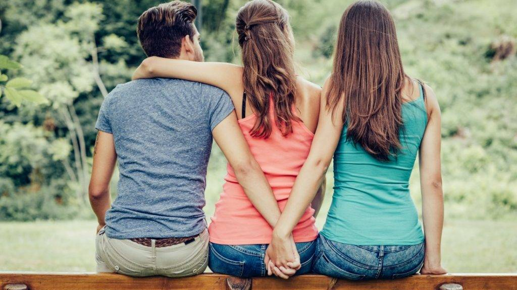 Love triangle, a girl is hugging a guy and he is holding hands with another girl, they are sitting together on a bench