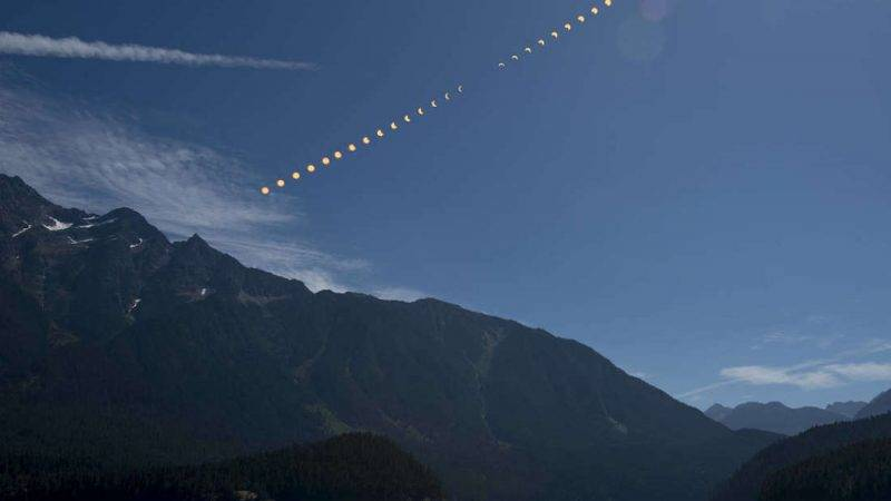 This composite image shows the progression of a partial solar eclipse over Ross Lake, in Northern Cascades National Park, Washington on Monday, Aug. 21, 2017. A total solar eclipse swept across a narrow portion of the contiguous United States from Lincoln Beach, Oregon to Charleston, South Carolina. A partial solar eclipse was visible across the entire North American continent along with parts of South America, Africa, and Europe.  Photo Credit: (NASA/Bill Ingalls)