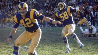 LOS ANGELES - DECEMBER 22:  Linebacker Isiah Robertson #58 of the Los Angeles Rams follows behind the block of safety Dave Elmendorf #42 on a 59-yard interception return for a touchdown against the Washington Redskins in the 1974 NFC Divisional Playoff Game at the Los Angeles Memorial Coliseum in Los Angeles, California on December 22, 1974.  The Rams defeated the Redskins 19-10. (Photo by Nate Fine/Getty Images)