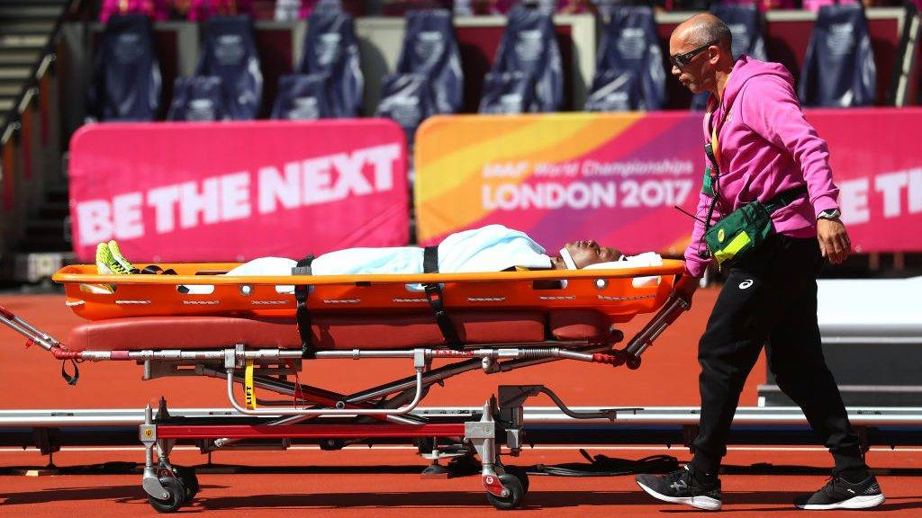 LONDON, ENGLAND - AUGUST 11:  An injured Deborah John of Trinidad and Tobago is given assistance after she falls in the Women's 100 metres hurdles heats during day eight of the 16th IAAF World Athletics Championships London 2017 at The London Stadium on August 11, 2017 in London, United Kingdom.  (Photo by Alexander Hassenstein/Getty Images - for IAAF)