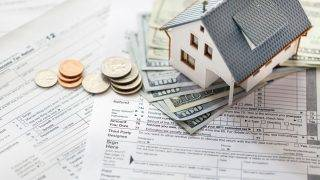 Photograph of tax forms with miniature house and money, selective focus.