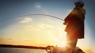 man fishing on a lake. Sunset