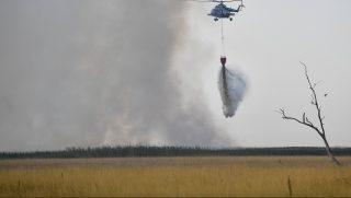 Nagyiván, 2017. augusztus 4. Honvédségi helikopterrel oltják a lángokat 2017. augusztus 4-én a Hortobágyon, Nagyiván térségében, ahol több száz hektáron ég a Hortobágyi Nemzeti Park. Az augusztus 3-án délelõtt keletkezett tûz oltásán egész éjjel dolgoztak a tûzoltók, augusztus 4-én kora reggel két, 3 ezer liter víz szállítására alkalmas honvédségi helikopter is érkezett a helyszínre, hogy bekapcsolódjon az oltásba. MTI Fotó: Czeglédi Zsolt