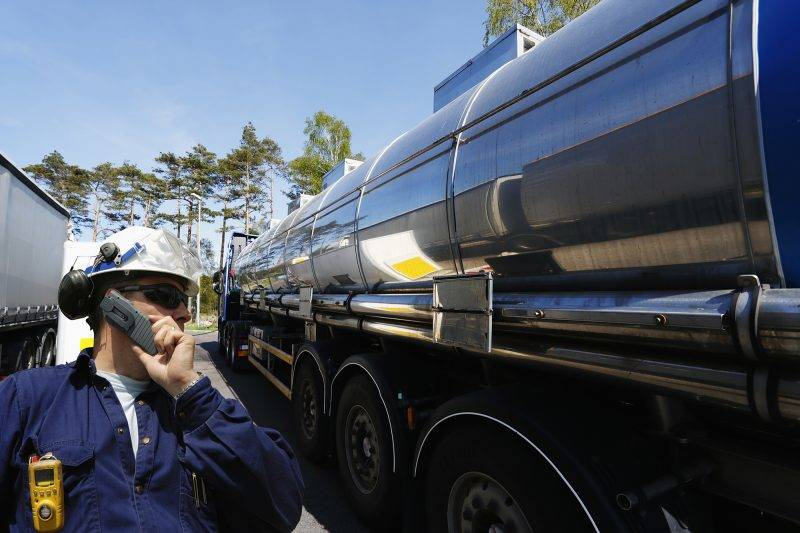 refinery worker talking in phone, large fuel-truck waiting for cargo