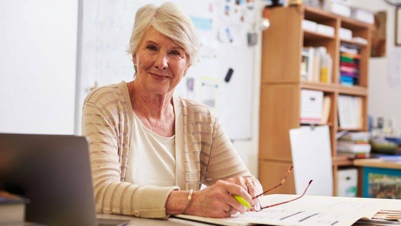 Portrait of senior female teacher working at her desk
