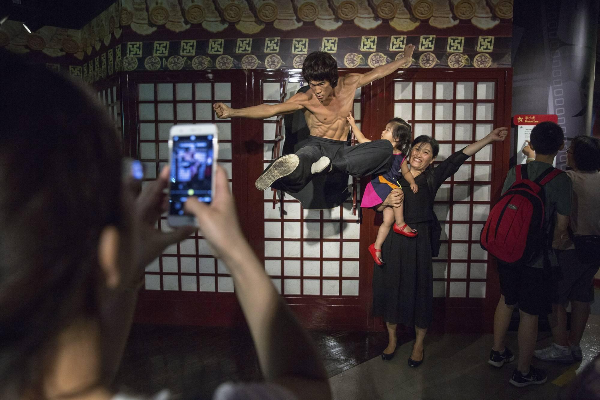 Peking, 2017. szeptember 8.Látogatók fényképezkednek Bruce Lee néhai hongkongi harcművész, színész viaszszobránál a Madame Tussauds panoptikumban, Pekingben 2017. augusztus 11-én. (MTI/EPA/Roman Pilipej)