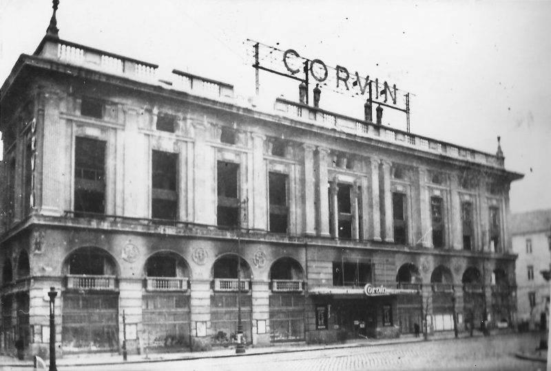A Corvin ¡ruh·z Èp¸lete l·thatÛ a kÈpen. Az utcakÈp ¸res. A tetőn emberi alakok l·thatÛak a Corvin felirat alatt.